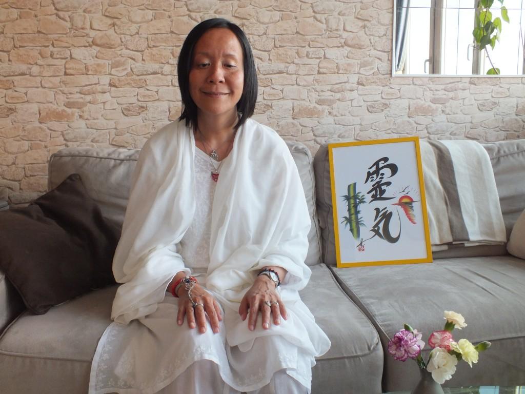 Photo d'Anne Yung, toute de blanc vêtue, assise à côté d'un tableau représentant l'idéogramme du Reiki.