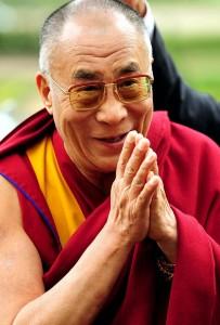 Le Dalaï Lama, les mains en prières, souriant