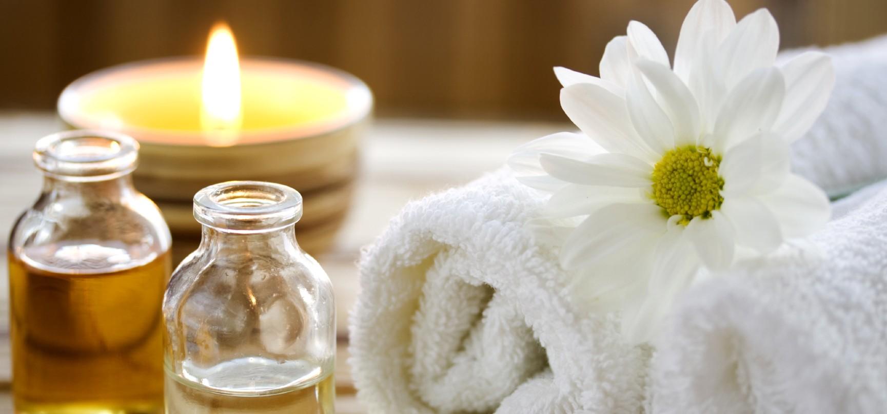 Huiles de massage, bougie et serviette