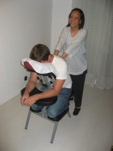 Anne effectuant un massage Amma assis sur un homme invité lors d'un événement privé