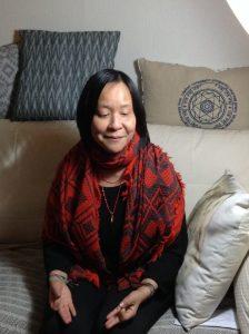 Portrait d'anne Yung, élégament vêtue de noir avec un foulard rouge.